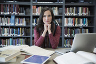Portrait confident adult education student researching in library - HEROF36034
