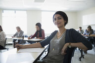 Portrait confident adult education student at desk in classroom - HEROF36037