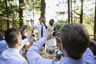 Man photographing bride and groom at wedding reception - HEROF36046