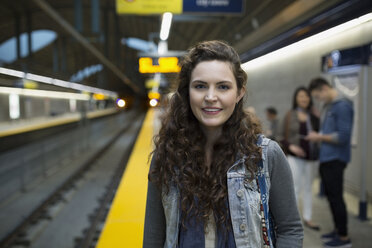 Portrait smiling young woman on subway station platform - HEROF36064