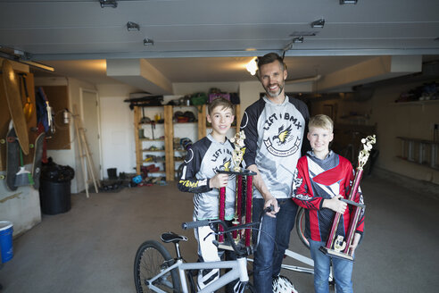 Portrait smiling father and sons with BMX bike trophies in garage - HEROF36100
