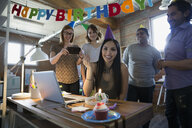 Portrait smiling businesswoman enjoying birthday party with coworkers in office - HEROF36130