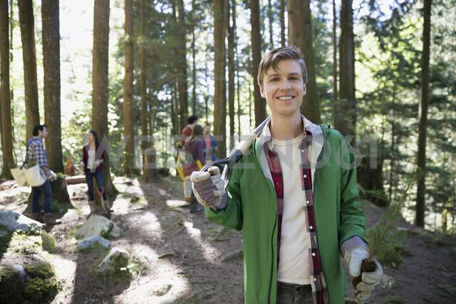Portrait smiling volunteer planting tree in woods - HEROF36172 - Hero Images/Westend61