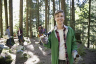 Portrait smiling volunteer planting tree in woods - HEROF36172