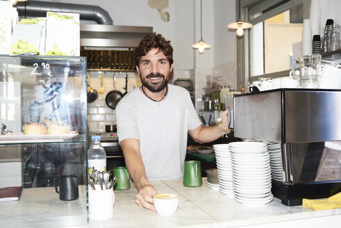 Portrait of smiling barista at the counter of a coffee shop - IGGF01153