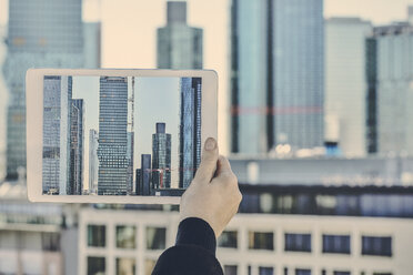 Germany, Frankfurt, hand taking photo of financial district with tablet - FMKF05538