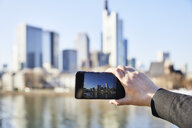 Germany, Frankfurt, hand taking photo of financial district with cell phone - FMKF05541