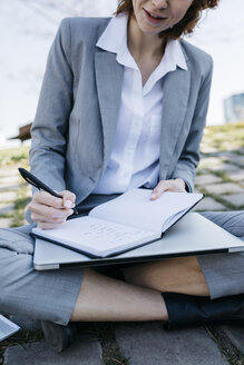 Businesswoman in the city, sitting on ground, writing in notebook - JRFF03029