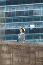 Successful young businesswoman standing at wall in front of office building - JRFF03035