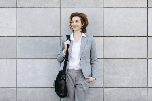 Portrait of a young confident businesswoman in front of wall with gray tiles - JRFF03062
