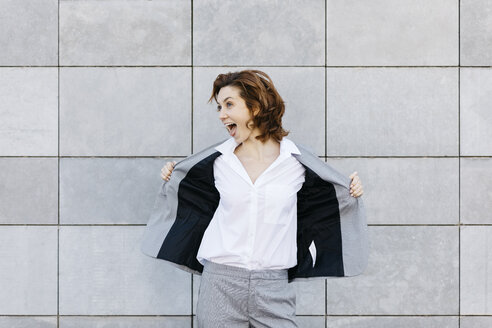 Portrait of a screaming young businesswoman in front of wall with gray tiles, opening her jacket - JRFF03065