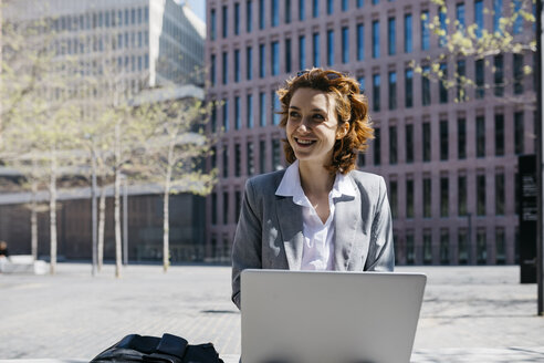 Young businesswoman with red shoes, sitting on a bench in the city, working on laptop - JRFF03068