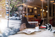 Portrait of smiling young man with earphones and smartphone behind windowpane in a restaurant - OCMF00401