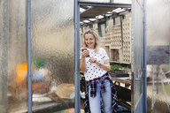 Young woman at a greenhouse, looking on her mobile phone - HMEF00310