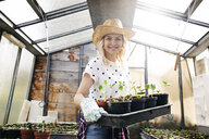 Young woman gardening in a greenhouse - HMEF00319