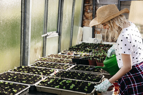 Young woman gardening in a greenhouse - HMEF00322
