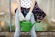 Young woman holding green watering can - HMEF00325