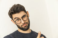 Portrait of doubting young man with beard and glasses - TCF06078