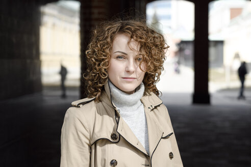 Portrait of woman with curly hair wearing beige trenchcoat and turtleneck pullover - EYAF00147