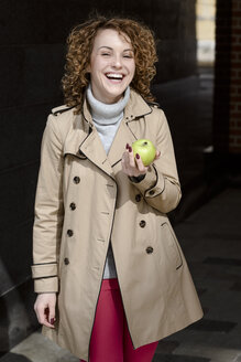 Portrait of laughing woman with green apple wearing beige trenchcoat and turtleneck pullover - EYAF00150
