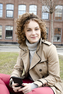 Portrait of smiling woman with smartphone wearing trenchcoat sitting on a meadow - EYAF00156