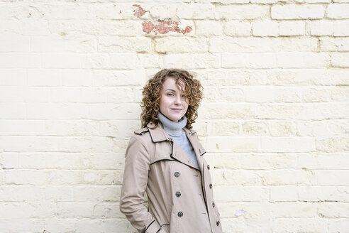 Portrait of young curly woman in trench coat near yellow wall - EYAF00159