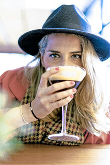 Woman drinking a coffee cocktail in a cafe - ERRF01075