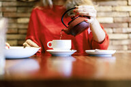 Close-up of woman pouring tea into cup in a cafe - ERRF01111