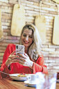 Smiling woman using cell phone in a cafe - ERRF01114