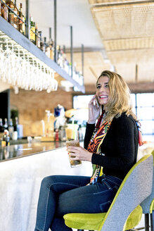 Smiling woman with cocktail and cell phone sitting at the counter of a bar - ERRF01135