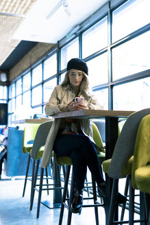 Woman sitting in a cafe using cell phone - ERRF01139