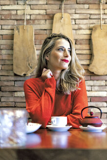 Smiling woman sitting at table in a cafe - ERRF01142