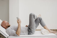Smiling man lying on lounge using cell phone - LHPF00525