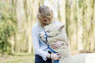 Woman cuddling alpaca - FLLF00115