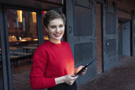 Germany, Berlin, portrait of confident businesswoman with digital tablet outdoors - TAMF01277