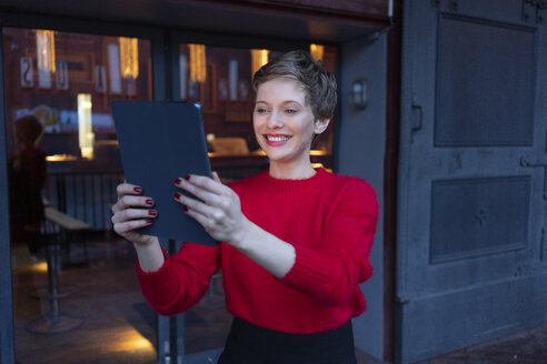 Portrait of smiling businesswoman taking selfie with digital tablet outdoors - TAMF01280