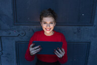 Portrait of smiling businesswoman with digital tablet at twilight - TAMF01283