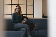 Businesswoman sitting on couch with laptop and takeaway coffee - GUSF01852