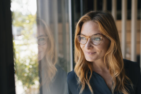 Portrait of smiling businesswoman looking out of window - GUSF01858