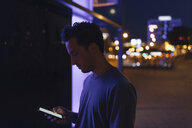 Young man using cell phone in the city at night - GUSF01867