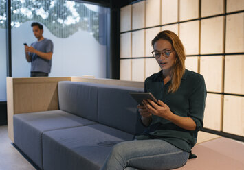 Young woman sitting on couch using tablet with man in background - GUSF01888