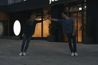 Young couple supporting each other in the city at night - GUSF01894