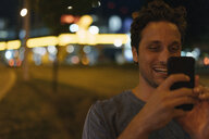 Happy young man using cell phone in the city at night - GUSF01903