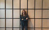 Portrait of smiling businesswoman standing at lockers - GUSF01909