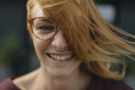 Portrait of happy young woman with glasses and windswept hair - GUSF01933