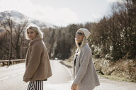 UK, Scotland, two happy young women on a country road - LHPF00540