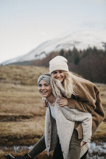 UK, Scotland, happy young woman carrying friend piggyback in rural landscape - LHPF00546