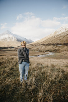 UK, Scotland, Loch Lomond and the Trossachs National Park, young woman standing in rural landscape - LHPF00561