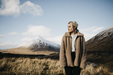 UK, Scotland, Loch Lomond and the Trossachs National Park, pensive young woman standing in rural landscape - LHPF00564
