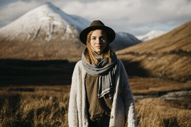 UK, Scotland, Loch Lomond and the Trossachs National Park, portrait of young woman wearing a hat in rural landscape - LHPF00567